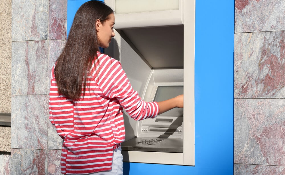 Woman using an ATM to make a deposit