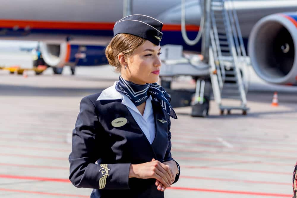 A young female flight attendant stands on duty on the tarmac of an airport.