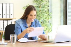 Happy woman reading bank account statement after receiving a signup bonus