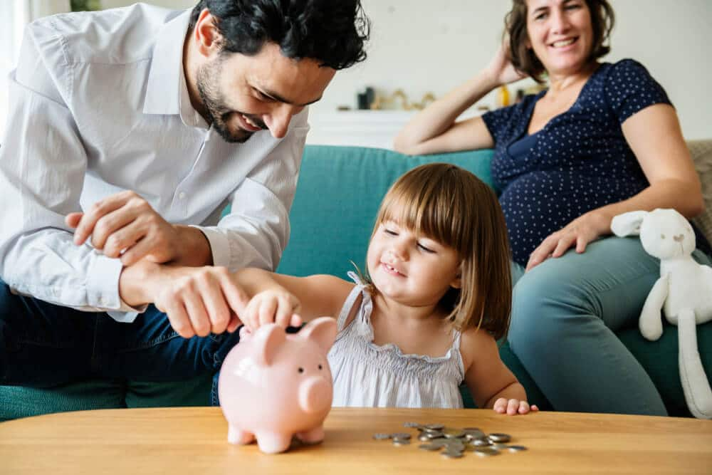 Parents helping young daughter put money in piggy bank