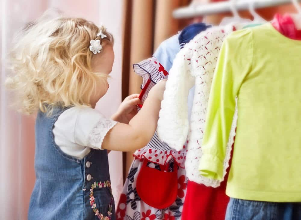 Little girl looking at clothes