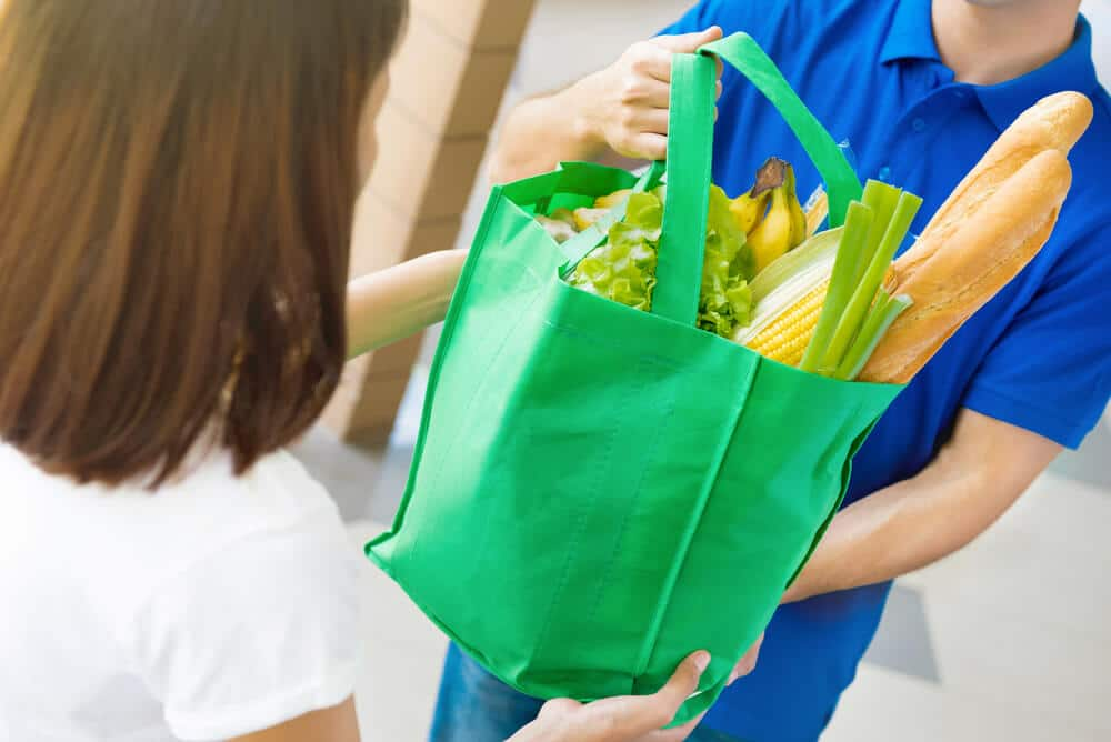 Woman receiving a buy now, pay later food delivery