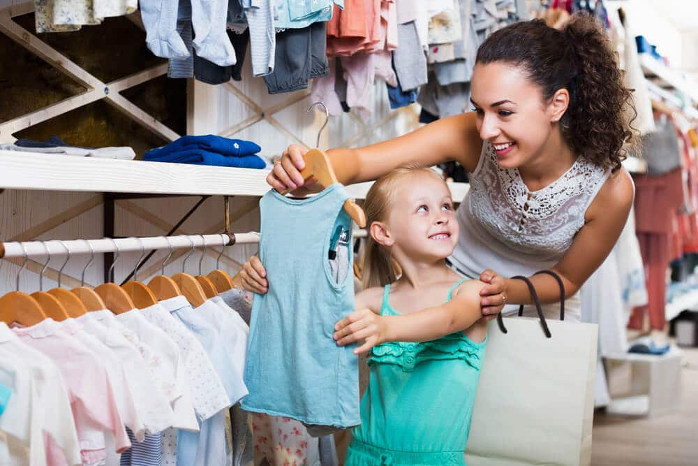 Young mother shopping at a buy now, pay later kids store with her daughter
