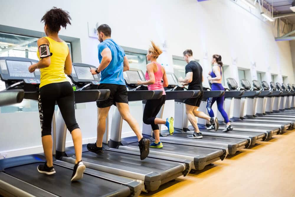 A group of people using treadmills at a gym