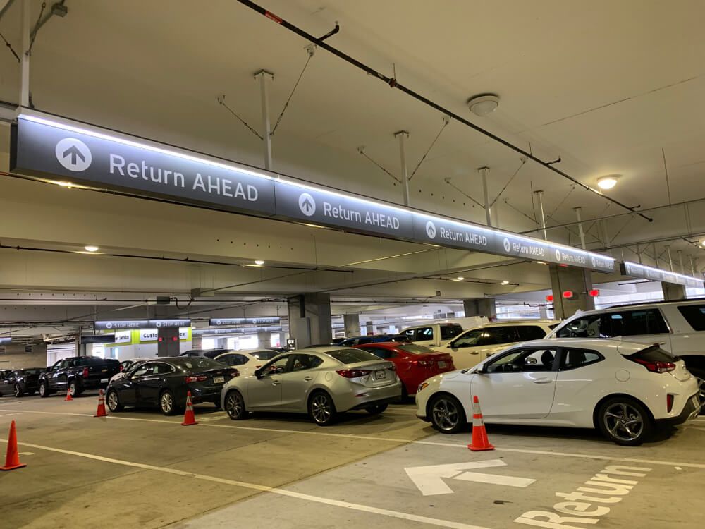 Parking garage with signs for car rental return ahead