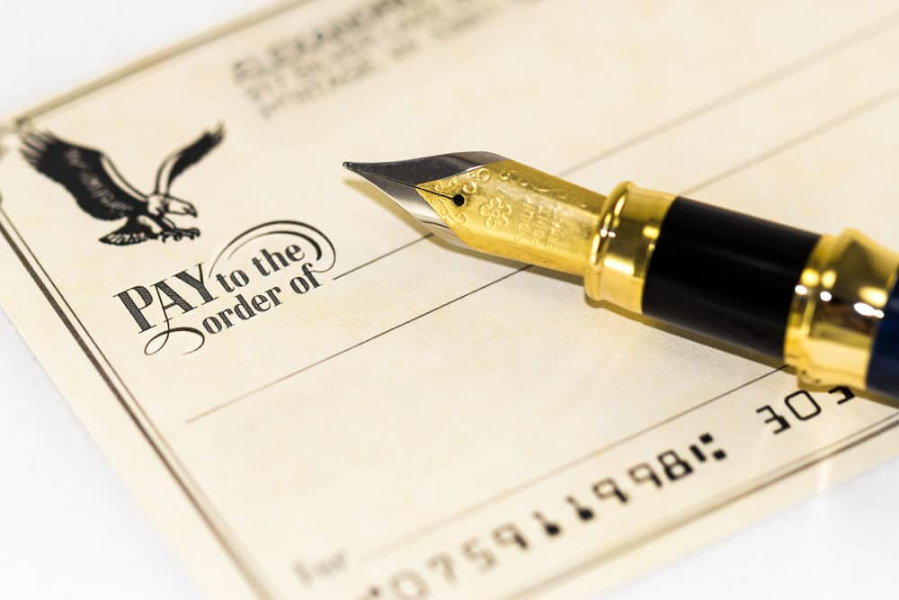 "Close-up of a pen resting on the ""Pay to the Order of"" field of a blank check"