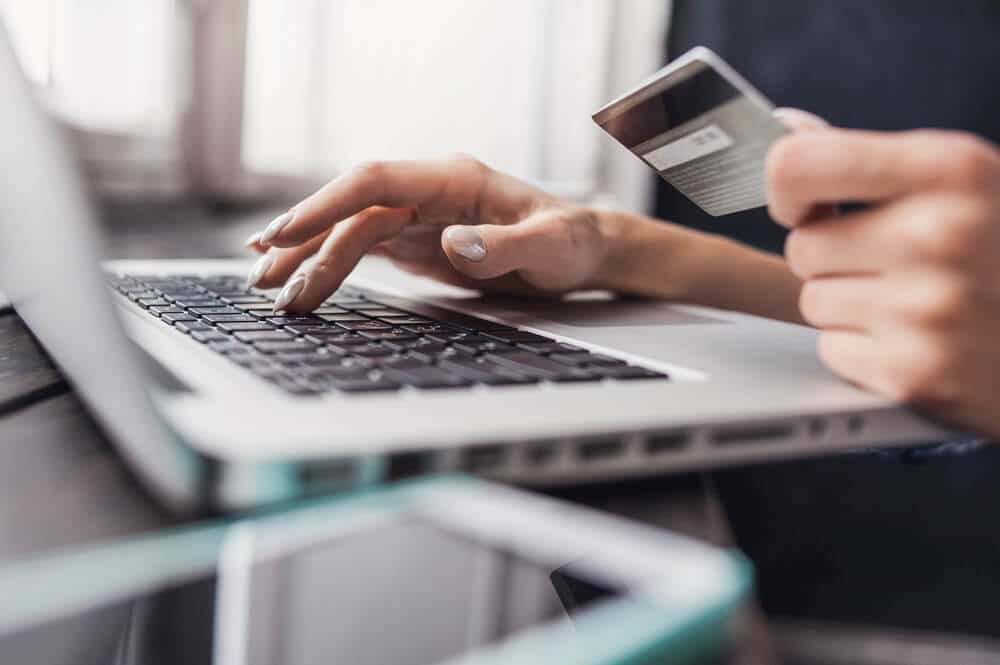 Woman holding a credit card with one hand and typing on a laptop with the other