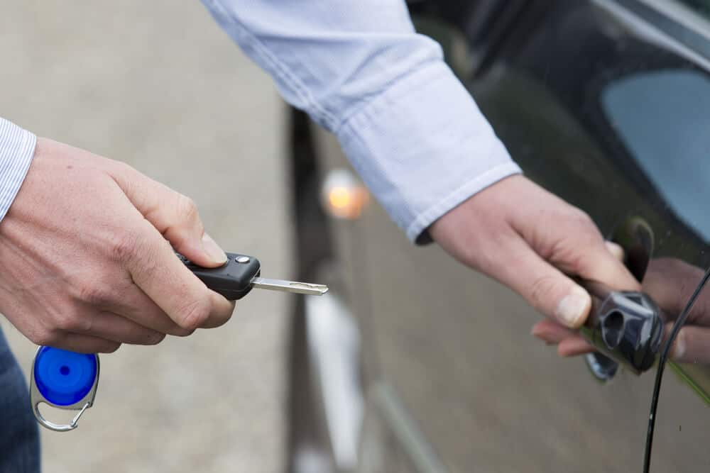 Man unlocking a by-the-hour rental car and opening the door