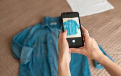Woman taking photo of shirt with her smartphone to post on a clothes swap app