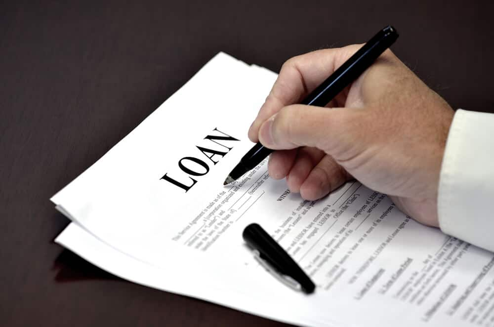 A person signs a loan agreement