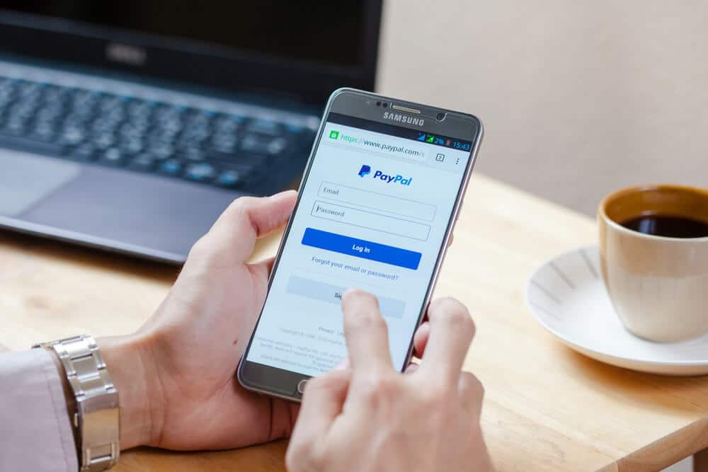 Man using a smartphone to log into PayPal