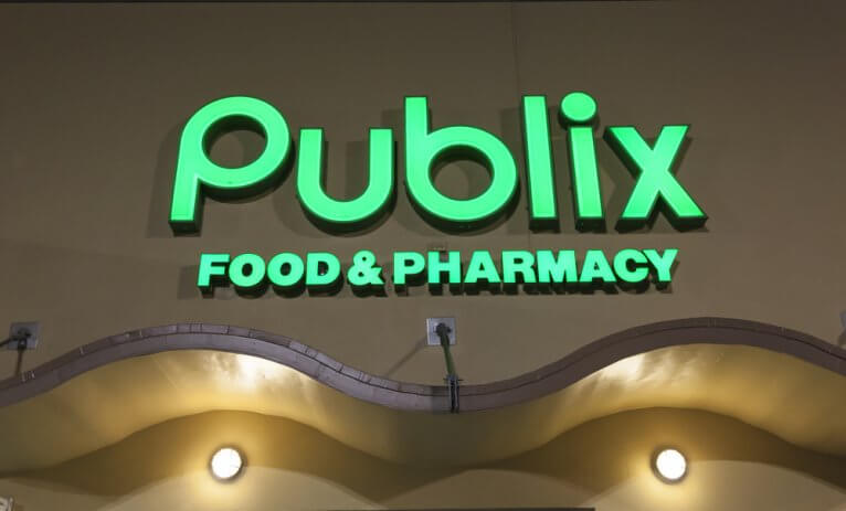"A lit green sign reading ""Publix Food & Pharmacy"" on the outside of a Publix store"