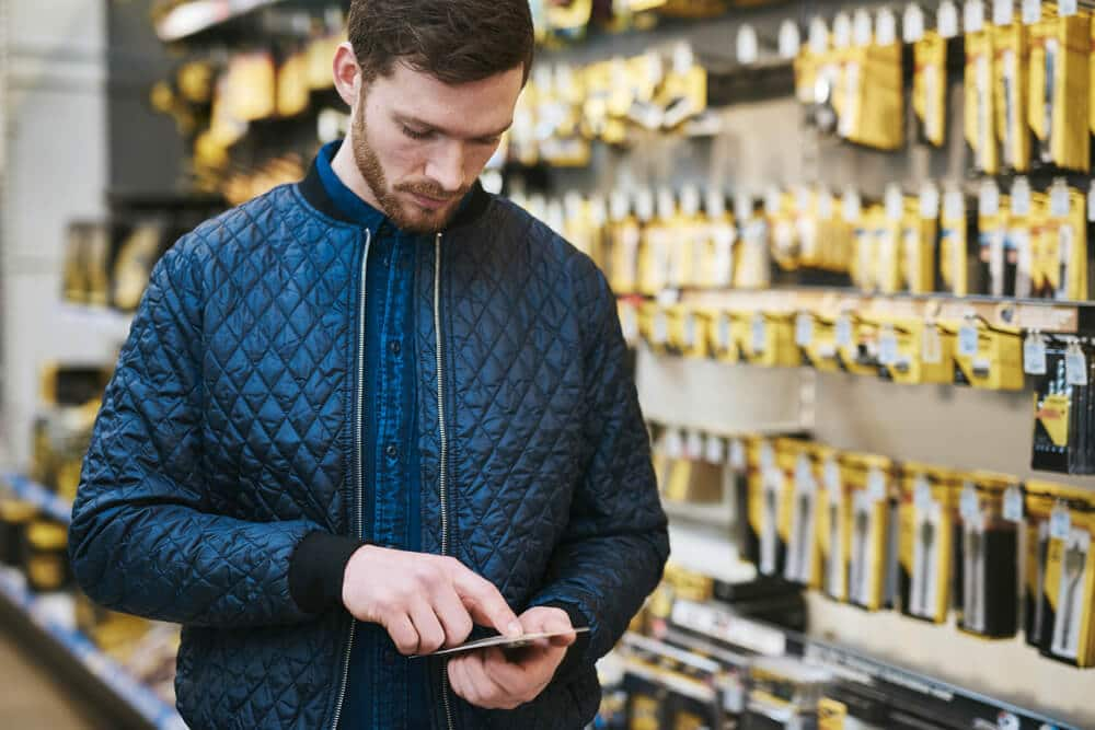 A man checks competitor prices on his phone in an isle of Sportsman's Warehouse.