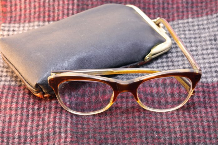 A pair of old glasses next to a leather case