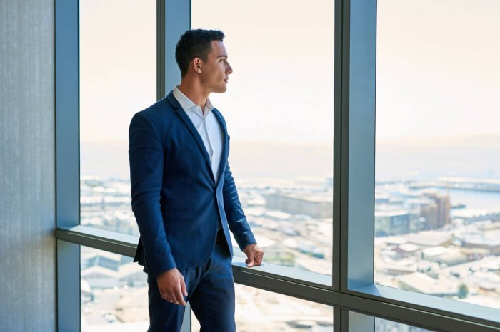 A career-driven man looks out of a tall building and into the future while he contemplates his goals.