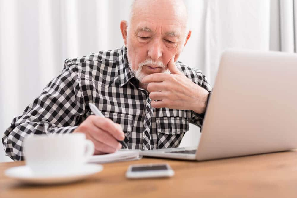 Man using laptop to take a free online class for seniors