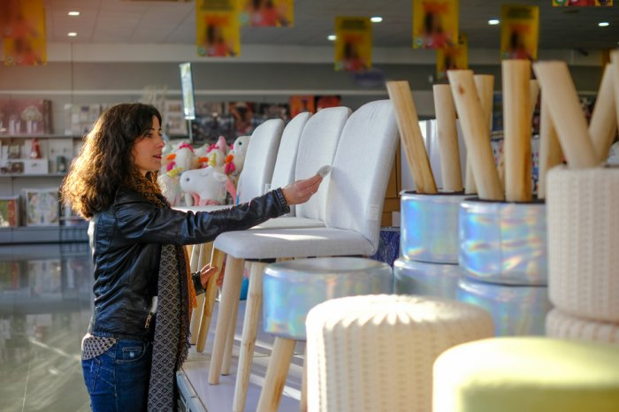 Woman shopping for chairs in a furniture store
