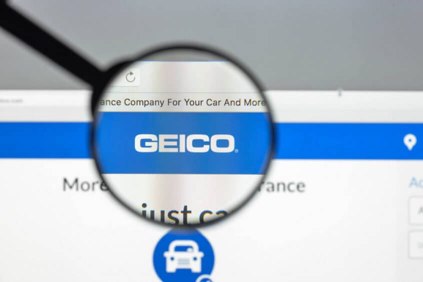 GEICO logo under a magnifying glass.
