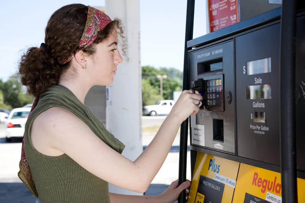 Woman paying with a credit card at the gas pump