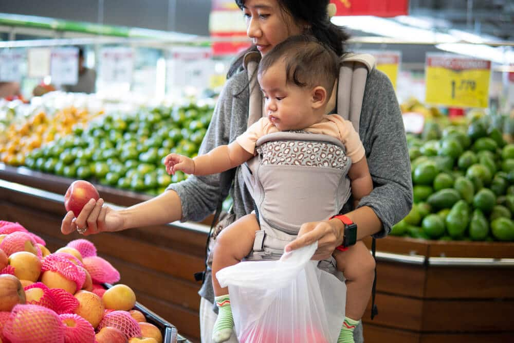 Woman and baby shopping at a grocery store that accepts WIC