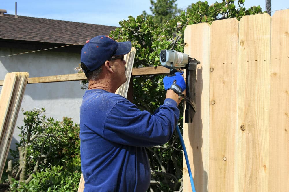 A professional installs a fence as a contractor for either Lowe's or The Home Depot.