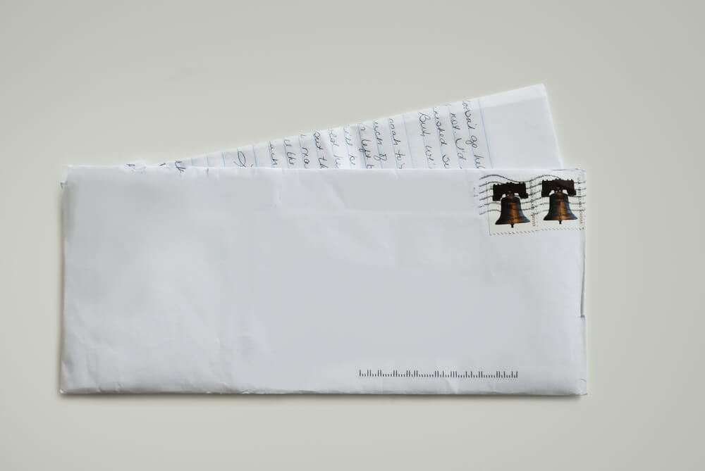 Unaddressed white envelope with two stamps in the upper right corner