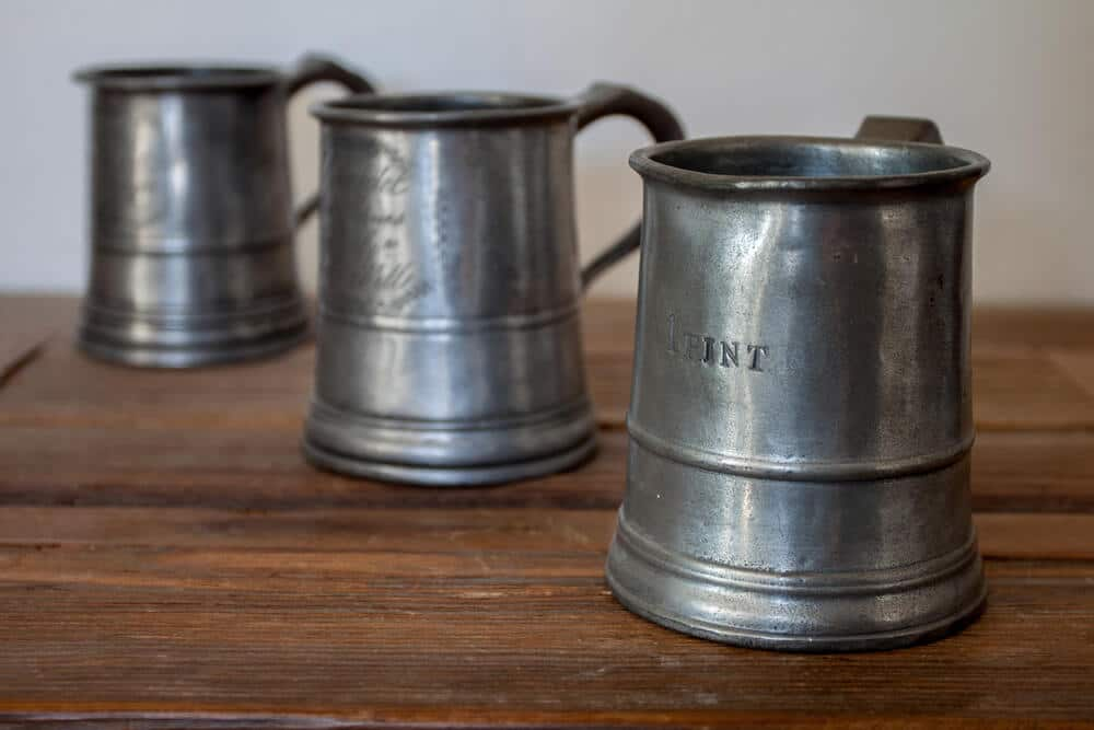 Three pewter mugs on a wooden table