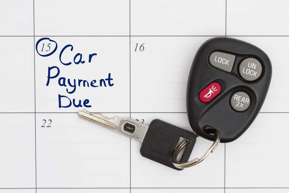 Car key resting on calendar with car payment due date