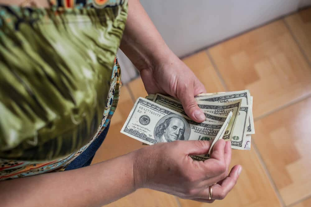 Woman counting cash after cashing a money order