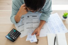 Man looking over financial documents and making a play to pay off debt