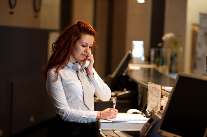 A woman standing at the front desk of a hotel takes a phone call from someone who's paying for someone else's stay.