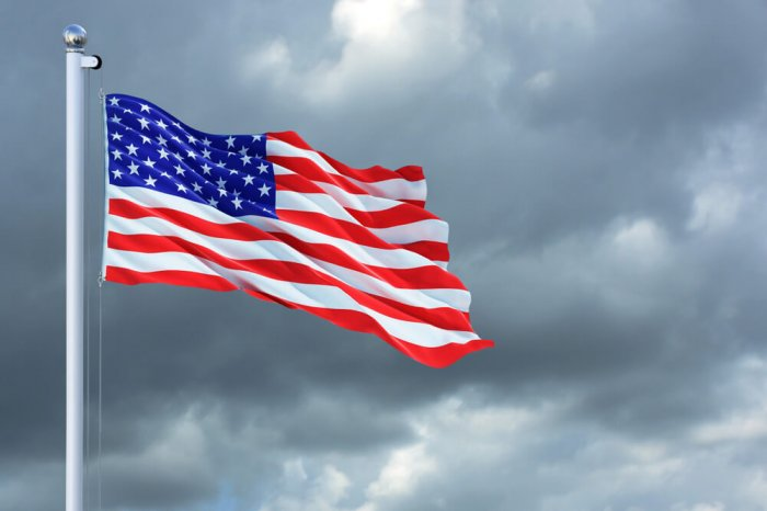 American flag waving on flag pole with cloudy sky