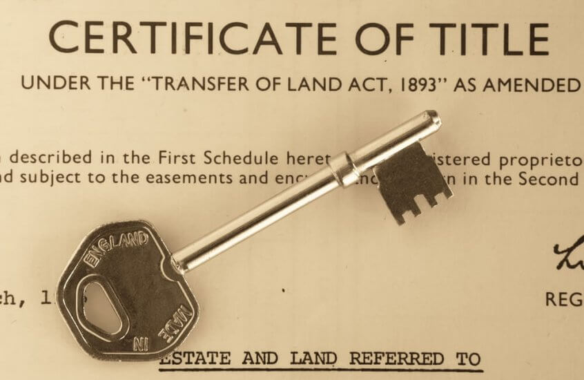 Image of a home title certificate with a key on top of it.