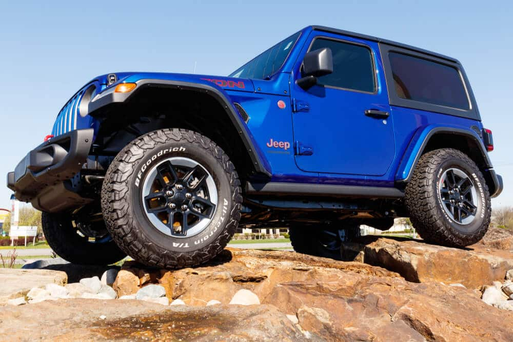 Blue jeep on a driving on a rock formation