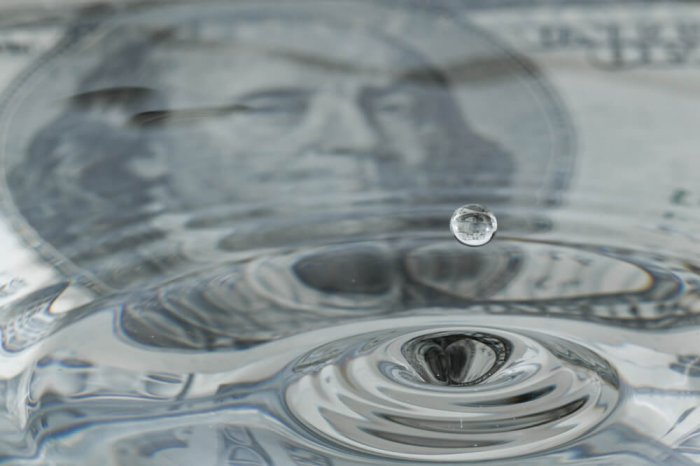 A U.S. bill with water on top of it to represent liquid assets.