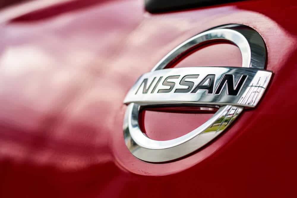 Closeup of a Nissan logo on a red Nissan car that was financed.