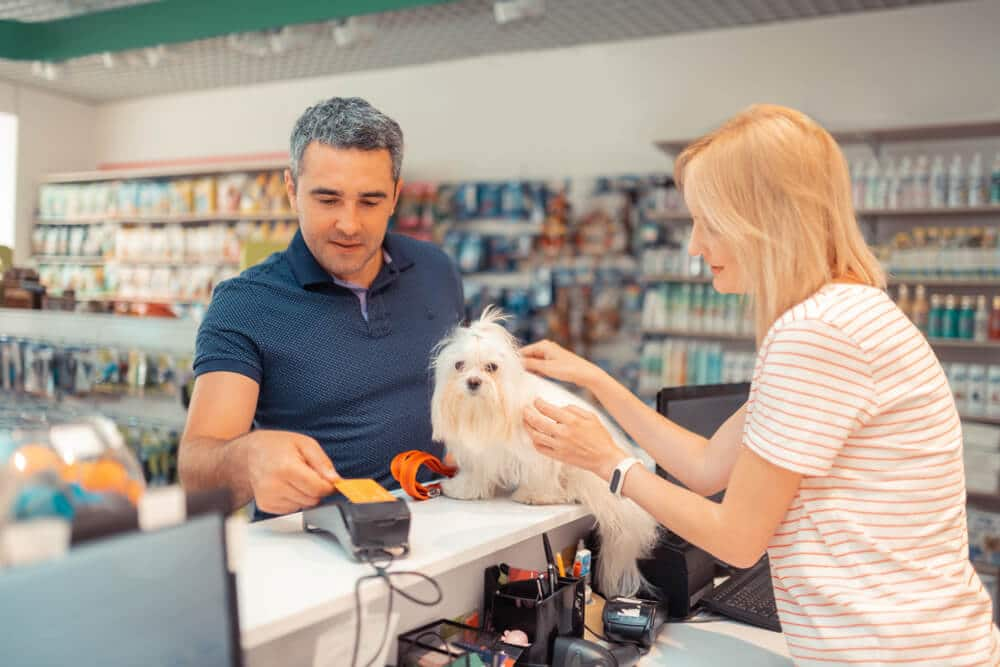 Man paying for purchase at a pet store with a credit card