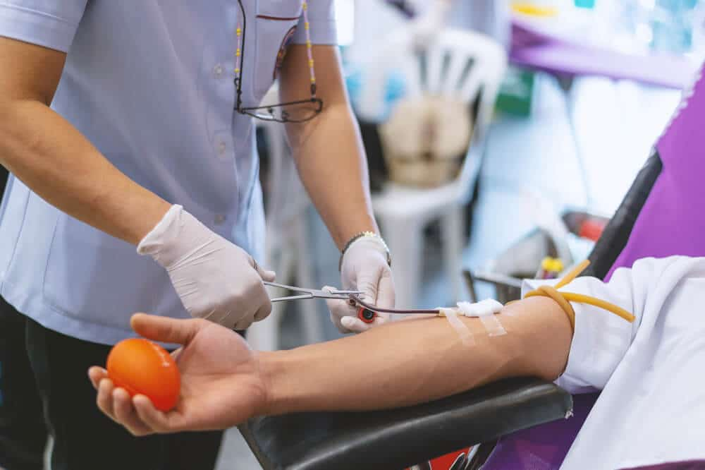 Woman adjusting tubing in donor's arm as donor prepares to give blood or plasma