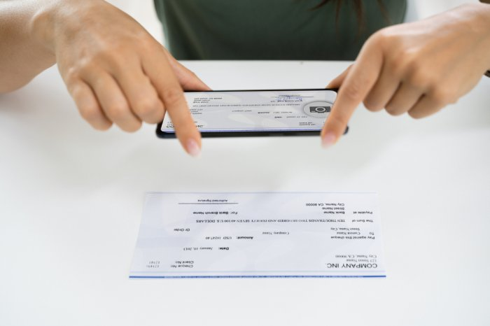Woman using a smartphone to mobile deposit a check