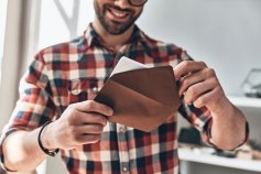 Man removing a printable gift certificate from a brown envelope