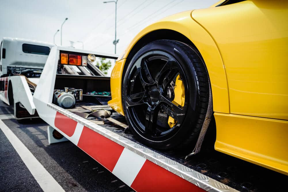 Sports car loaded onto a tow truck after repossession