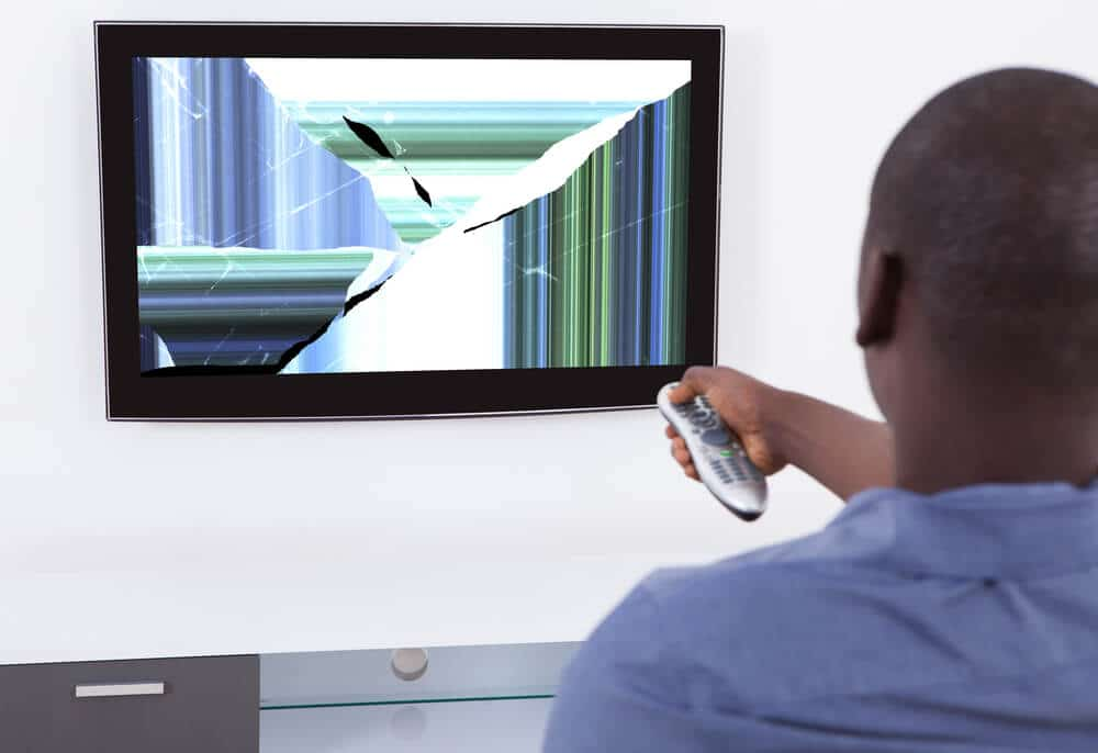 Man pointing remote at broken TV with distorted screen