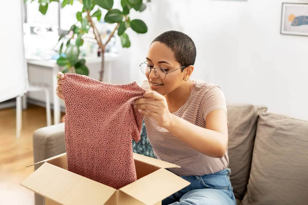 Woman opening a clothing delivery from a site or app like Poshmark