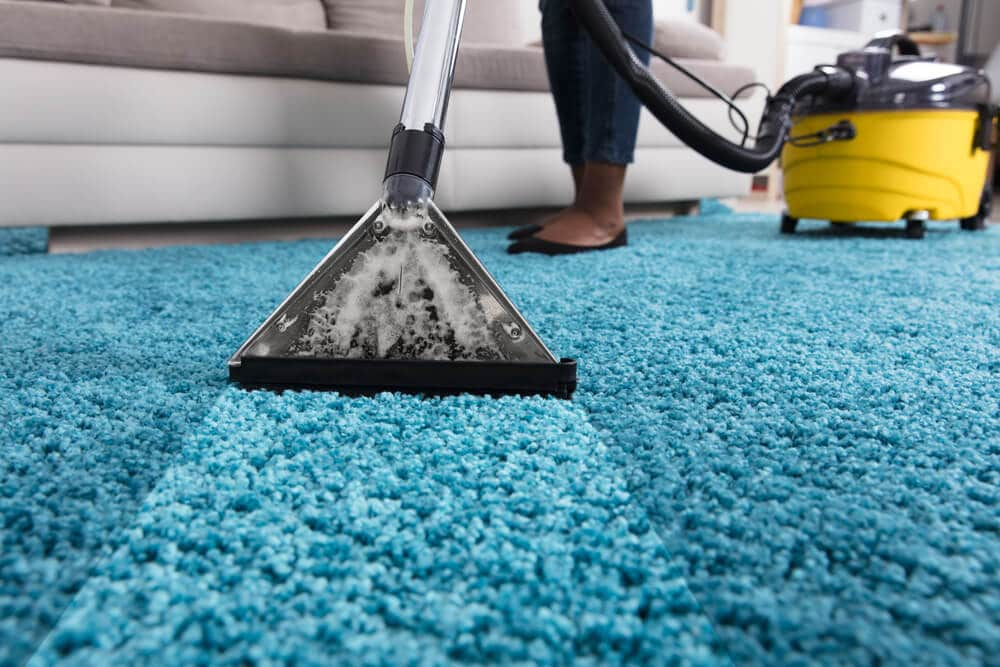 Person using a carpet cleaner on a rug