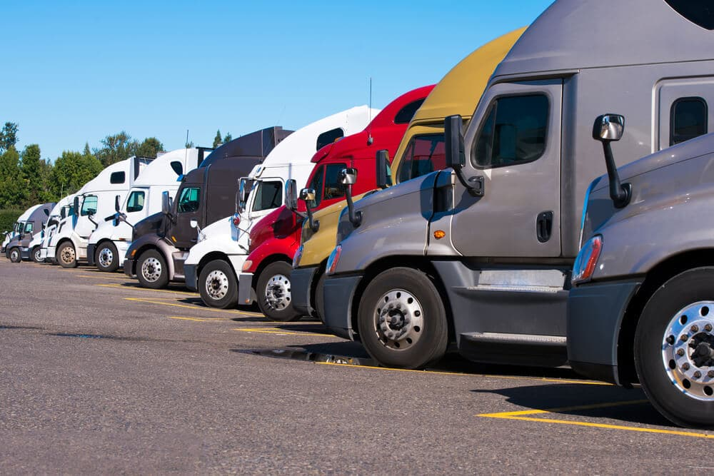 A row of semitrucks parked at a truck stop