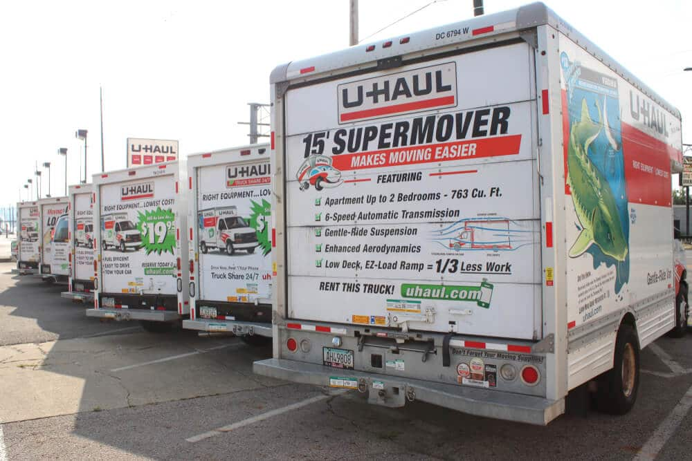 A row of parked U-Haul moving trucks