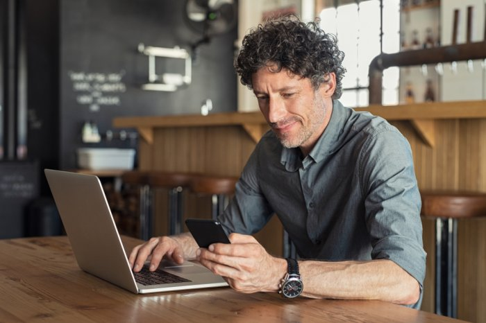 Man using a virtual debit card to shop online with a smartphone and laptop