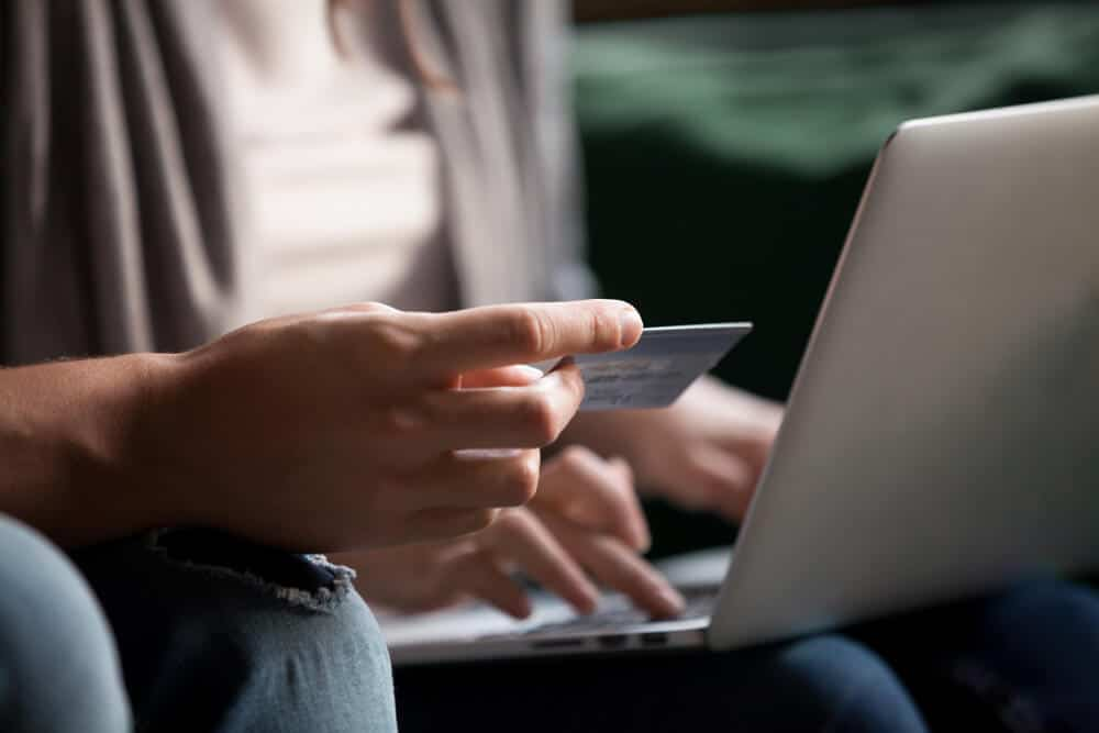 Person holding a debit card and laptop