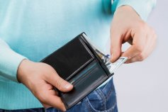 Person removing money from wallet to pay for a money order