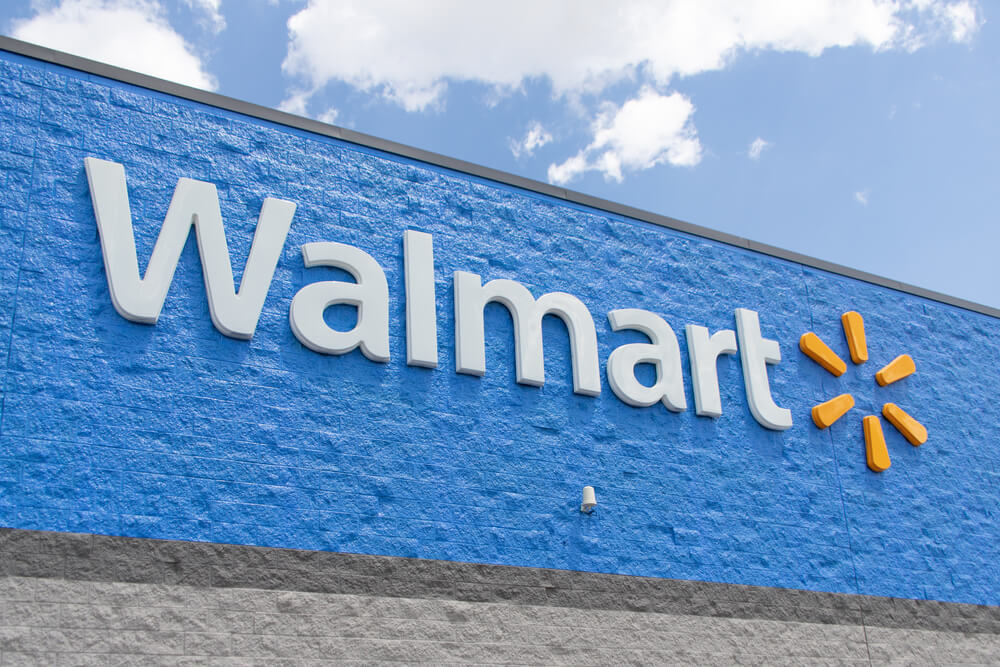 White and yellow logo sign on the outside of a Walmart store